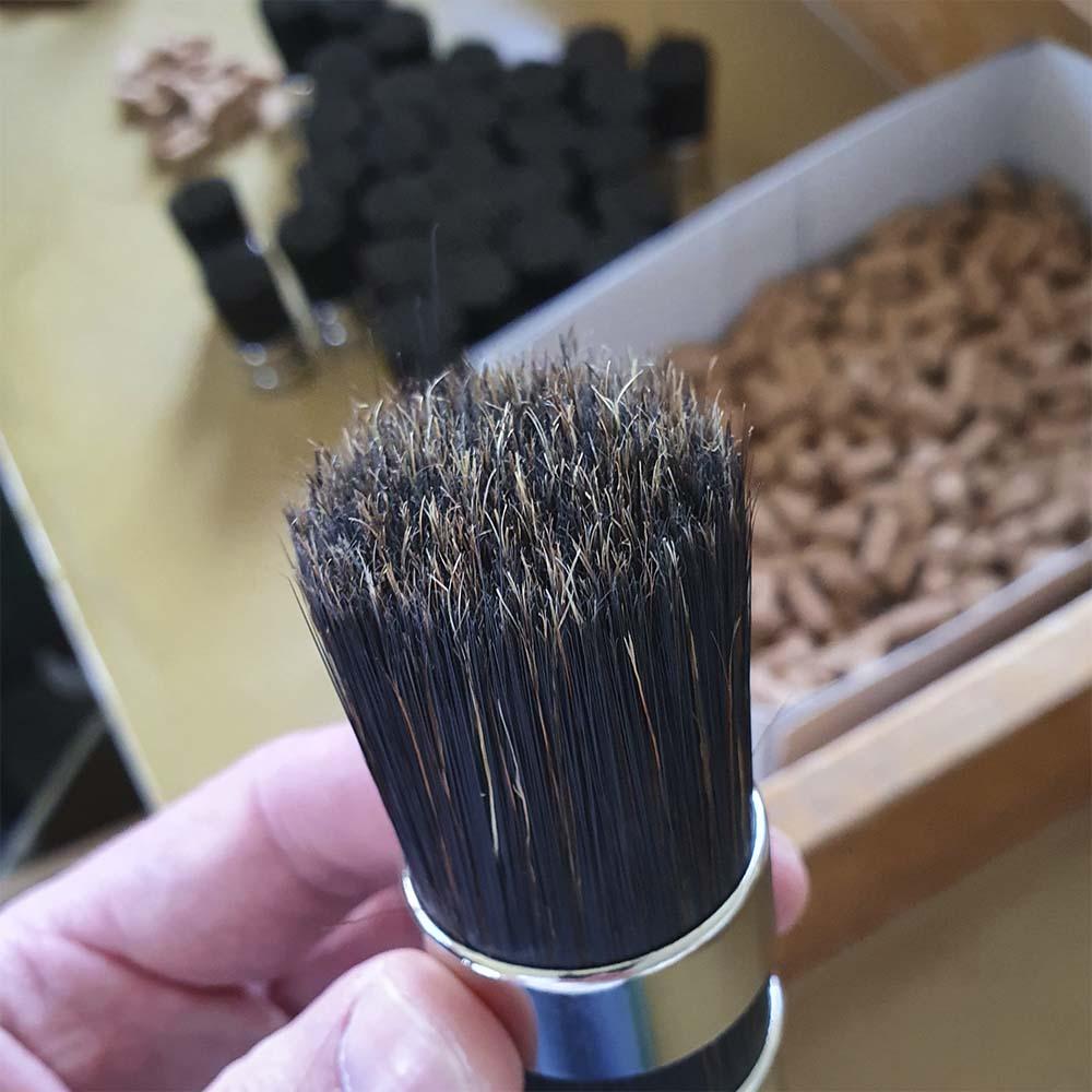 Traditionelle Pinsel-Produktion in Handarbeit: Ein Pinselmacher mit fertig zusammengesetzten Pinsel-Kopf in der Hand an seinem Arbeitsplatz
