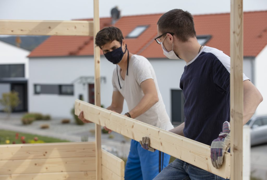 Zwei Handwerker tragen eine Maske während sie im Freien einen Holzbalken an seine Stelle setzten.