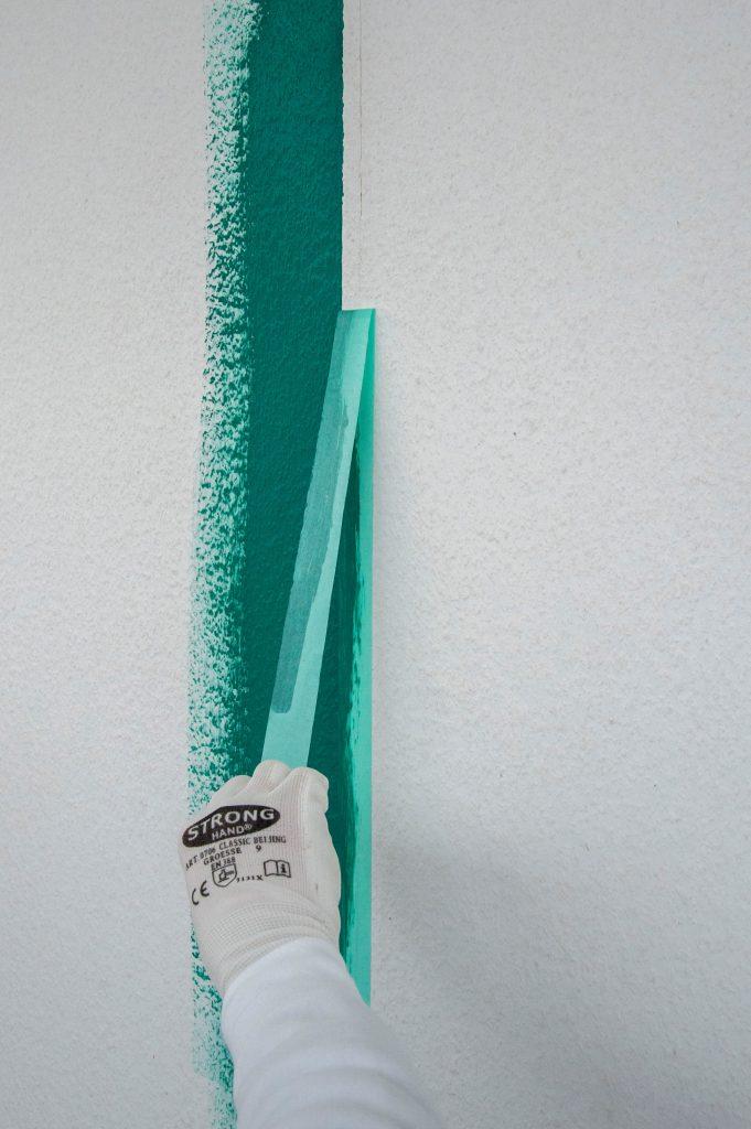 Blaues Washi-Tape wird nach dem streichen sorgfältig abgezogen